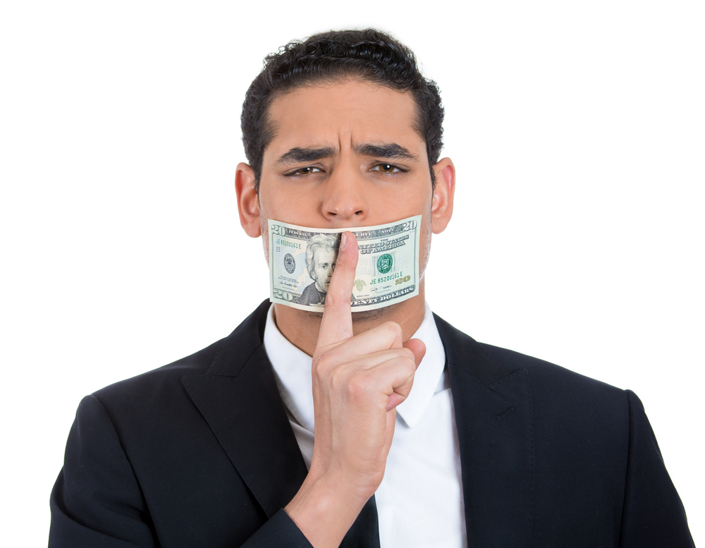 Man in black suit with twenty dollar bill taped to mouth and showing shhh sign, isolated on white background.